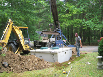 A septic tank is lowered into the ground at a Pike County Pennsylvania home by a Septic Medic technician